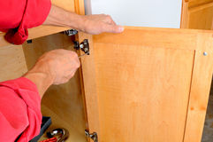 Attaching Hinge to Cabinet. Closeup of a installers hands attaching a hinge a kitchen cabinet stock photos