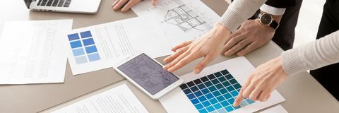 Closeup interior designers working with color swatches palette and blueprint stock photography