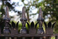 Closeup of iron fence. Old iron fence with spikes on top, visibly aged where the paint has disappeared Stock Photography