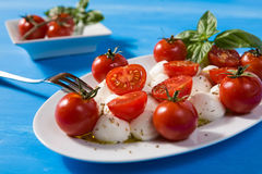 Closeup of Italian caprese with mozzarella, cherry tomatoes and Royalty Free Stock Images