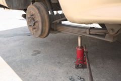 Closeup of jacked car. Abstract closeup of rusty drum brake of light truck with wheel removal on top of jack Stock Image