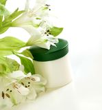 Closeup of jar of moisturizing face cream and flow Royalty Free Stock Photo