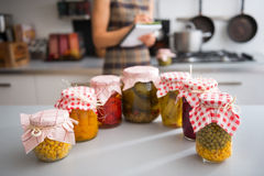 Closeup on jars of pickled vegetables and housewif stock image
