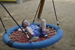 Joung boy on swing during summer time royalty free stock images