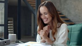 Joyful business lady analysing financial report. Smiling woman working in office