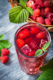 Closeup of juice with fresh raspberries and ice. On old table Stock Photography