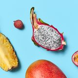 Closeup of juicy pineapple slices, pitahaya, passion fruit, and ripe mango on a blue background with space for text stock photos