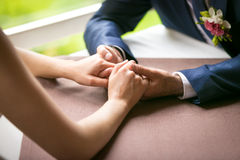 Closeup of just married couple holding hands at restaurant Royalty Free Stock Photos
