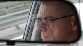 Старший человек управляет автомобилем на проселочной дороге Отражение стороны в зеркале заднего вида автомобиля closeup 4K видеоматериал