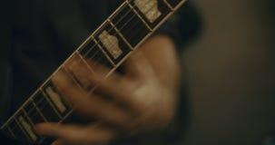 Closeup 4K av fingrar som spelar en elektrisk elbas i en hem- studio lager videofilmer