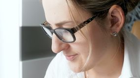 Closeup 4k footage of beautiful businesswoman wearing eyeglasses woking in office and typing on computer. Closeup 4k video of beautiful businesswoman wearing stock video footage