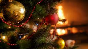 Closeup 4k video of beautiful decorated Christmas tree with red and golden baubles against burning fireplace. Perfect