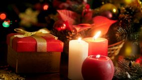 Closeup 4k footage of burning candles and gift box with present for Christmas stock video