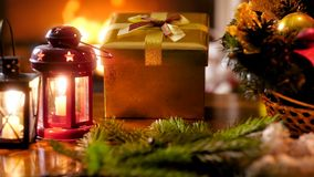 Closeup 4k footage of Christmas wreath, candle lantern and New Year present from Santa on wooden table against burning