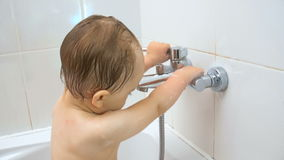 Closeup 4K footage of cute toddler boy opens water faucet at bathroom stock footage