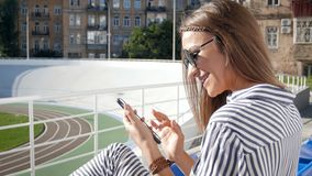 Closeup 4k footage of stylish young woman sitting on stadium at sunny day and using mobile phone. Closeup 4k video of stylish young woman sitting on stadium at stock footage