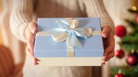 Closeup 4k footage of young woman holding beautiful box with gift tied with ribbon and bow. Family giving and receiving