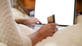 Closeup 4k footage of young woman holding credit card in hand while browsing intrnet and online stores. Concept shot of stock video footage