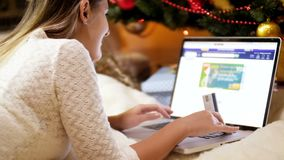 Closeup 4k footage of young woman holding credit card in hand and shopping online to order gifts and presents for stock footage