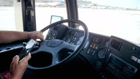 Closeup 4k video of bus driver at airport talking by phone while driving bus to airplane stock video footage