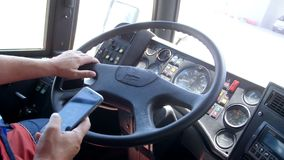 CLoseup 4k footage of public bus driver taking out mobile phone and browsing it. COncept of danger and irresponsibility stock video