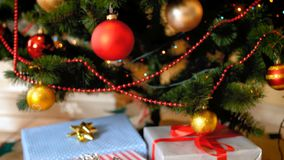 Closeup 4k footage of stack of gift boxes under Christmas tree at living room stock video