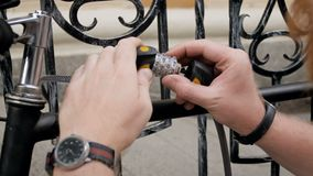 Closeup 4k footage of young man using combination lock and chain to protect his bicycle on street. Closeup 4k video of young man using combination lock and chain stock footage