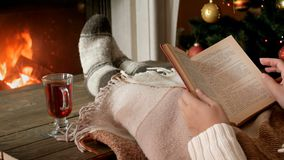 Closeup 4k footage of young woman lying with book in living room with burning fireplace and drinking hot tea stock video footage