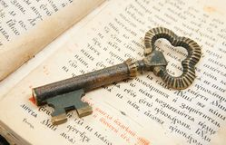 Closeup of key placed on vintage bible Stock Photo