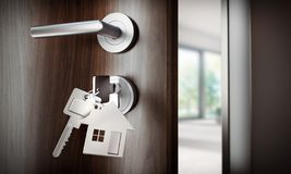Open door with keys agains an empty apartment royalty free stock photography