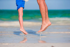 Closeup kid and adult feet jumping in shallow water on white sandy beach Stock Photo
