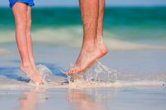 Closeup kid and adult feet on white sandy beach Stock Image