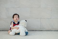 Closeup asian kid is crying with bear doll sit on brick wall textured background royalty free stock image