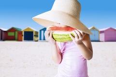 Closeup of kid enjoy watermelon at shore Stock Image
