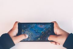 Closeup of kid hands playing video games on cell phone. Rayong, Thailand-January 14,2018:Closeup of kid hands playing video games on cell phone Royalty Free Stock Photography