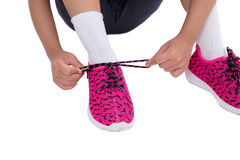 Closeup on kid hands tying her shoes. In isolated white background Royalty Free Stock Image