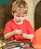 Closeup kid playing with metal bolts. Little laborer in workshop. Cute boy in red T-shirt behind the table.  Royalty Free Stock Images