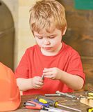 Closeup kid playing with metal bolts. Little laborer in workshop. Cute boy in red T-shirt behind the table.  stock image