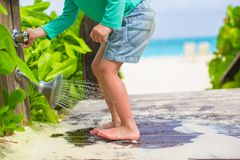 Closeup of kids legs under a beach shower in the Stock Photo