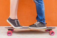 Closeup kissing couple at skateboard and red wall background Royalty Free Stock Images