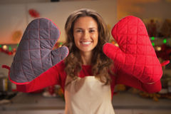 Closeup on kitchen gloves showing by young housewife in kitchen Stock Photography