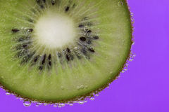 Closeup of a kiwi slice covered in water bubbles against a purple background Stock Images
