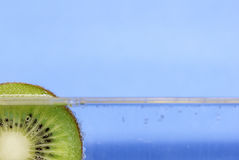 Closeup of a kiwi slice floating in sparkling water against an aqua blue background Royalty Free Stock Photos