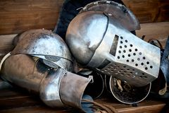 Closeup of a knight`s armor, helmet, glove and part of the trunk. Lie on a wooden bench after a tournament or battle. The concept of disarmament and peace Stock Photography