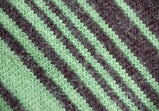 Closeup of knitted material. Closeup of brown and green  striped  knitted woolen material showing fibers and providing a colorful background Royalty Free Stock Photos