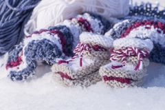 Closeup of knitted woolen baby booties made with love. Closeup with knitted baby booties of warm wool in snowy winter sunlight made with love Royalty Free Stock Photo