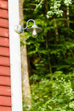 Closeup of lamp on wooden house in forest Royalty Free Stock Photo