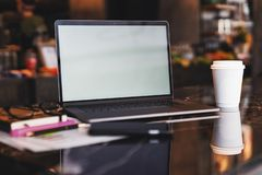 Closeup of laptop with blank monitor and cup of coffee on table in cafe. Empty workplace without people. Home office freelancer. Workspace student distance royalty free stock photo