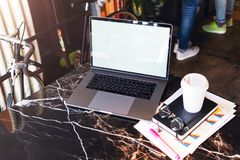 Closeup of laptop with blank monitor and cup of coffee on table in cafe. Empty workplace without people. Home office freelancer. Workspace student distance stock photography
