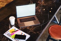 Closeup of laptop with blank monitor and cup of coffee on table in cafe. Empty workplace without people. Home office freelancer. Workspace student distance stock image